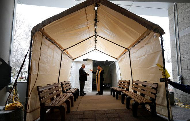 John Kalinowski, left, assists Hospital Chaplain Rev. Joseph Nguyen, right, as he blesses a medical triage tent that is being set-up outside of Mercy Hospital in South Buffalo Friday, March 27, 2020.  The tent which is not operational now, will be finished and ready for patients with Covid-19 in the near future.     (Mark Mulville/Buffalo News)