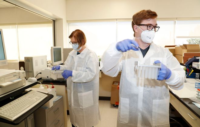 Clinical lab scientists, Theo Alger, right, and Suzi Maciejewski prepare to load a molecular analyzer to test a fresh shipment of samples at a Kaleida Health lab in Amherst. (Robert Kirkham/Buffalo News)