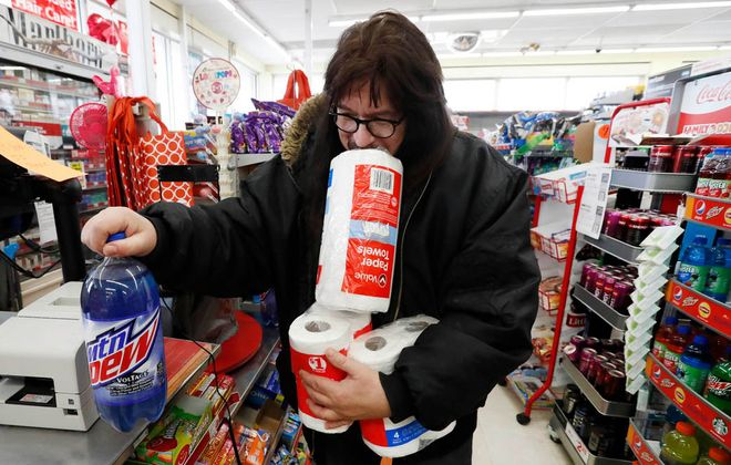 Tim Gerwitz, of Buffalo, stocks up with eight rolls of toilet paper, a roll of paper towels and two bottle of Mountain Dew at Familly Dollar on Kenmore Avenue in Buffalo, Friday, March 13, 2020.  (Sharon Cantillon/Buffalo News)