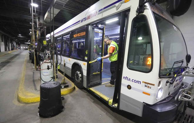 Daryl Phillips Jr. a bus maintenance helper wipes down high contact area's on a NFTA Metro bus with a 2 percent bleach and water solution at NFTA Cold Spring Bus Garage. (John Hickey/Buffalo News)