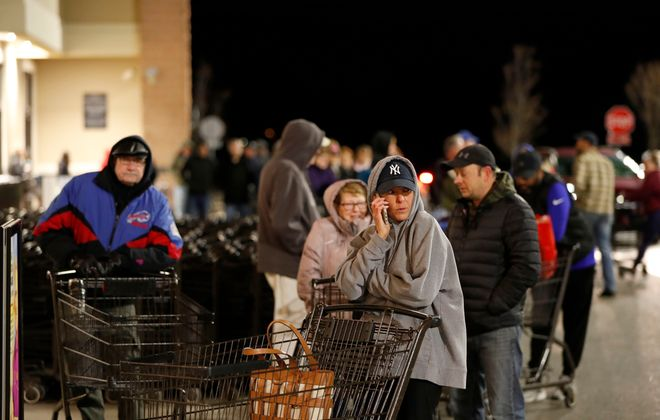 People wait in line to enter Wegmans in Hamburg before it opens at 6 a.m. Saturday. (Mark Mulville/Buffalo News)