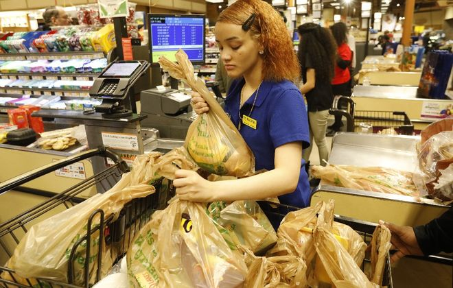 Supermarket employees are among the essential workers whose health needs to be protected. Wegmans and other supermarkets plan to install plexiglass shields to separate cashiers from customers. (Derek Gee/Buffalo News)