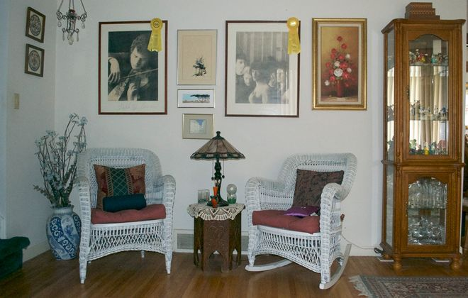 David J. W. Manny and Karen Tunis-Manny live in Snyder. Above, antique wicker chairs and Manny's award-winning artwork are found in the living room. (Photo courtesy David J. W. Manny)