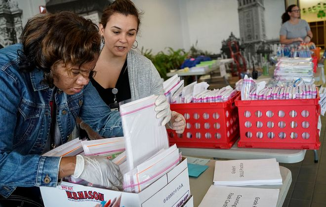Support staff Gabriella Harris, left, and teacher aide Jennifer Casillas look for a packet for a particular student as teachers and staff at Frederick Law Olmsted Elementary School PS64 send home classwork for students while schools are closed. (Derek Gee/Buffalo News)