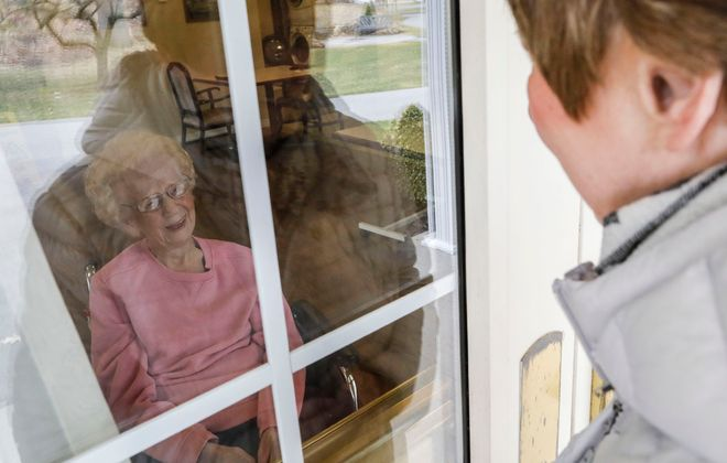 "Celestine ""Sally"" Szemenciak, 107, peers through a glass door at her daughter, Deanna Machtel, 76, who was standing outside the Beechwood nursing home in Amherst, where Szemenciak is a resident, on Tuesday, March 24, 2020. Visitors were banned from entering nursing home throughout New York State beginning March 13 as a precaution against the Covid-19 virus. (Derek Gee/Buffalo News)"