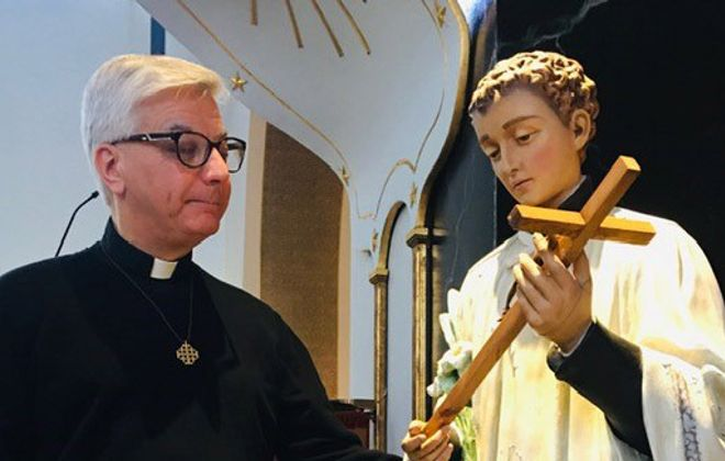 The Rev. Fred Betti with the statue of St. Aloysius Gonzaga in St. Michael's Catholic Church on Washington Street downtown. (Photo courtesy of Rev. Fred Betti)