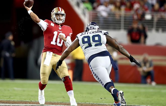 49ers quarterback Jimmy Garoppolo passes before being hit by Seattle's Quinton Jefferson in a game in 2019. (Ezra Shaw/Getty Images)