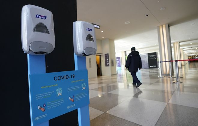 Hand sanitizers hang on the wall with a sign about COVID-19, also known as coronavirus, from the U.N. World Health Organization (WHO) at the United Nations Headquarters in New York City. (Timothy A. Clary/AFP via Getty Images)