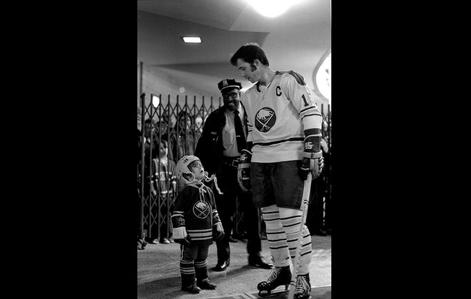 Dave Schofield's photograph of a young fan looking up admiringly at Sabres captain Gerry Meehan resonates across half a century because it captures something universal about the mythic pull of heroes. (Photo courtesy Dave Schofield)