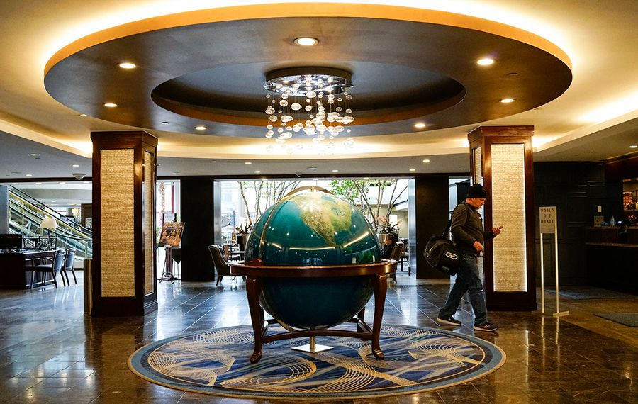 A guest walks through the lobby of the Hyatt Regency Buffalo, where disruption from the Covid-19 coronavirus pandemic has resulted in a dramatic loss of bookings, Friday, March 13, 2020. (Derek Gee/Buffalo News)