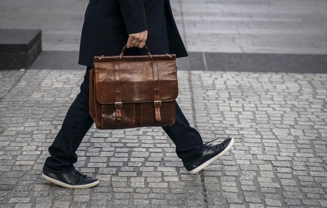 A man carries a briefcase as he walks through the Financial District in New York City. (Drew Angerer/Getty Images)