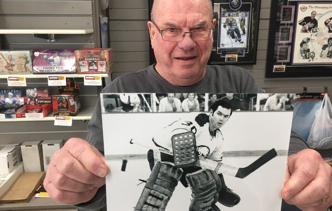 Joe Daley displays a picture from the 1970-71 season – when he played goal for the Sabres without wearing a mask. (Mike Harrington/Buffalo News)