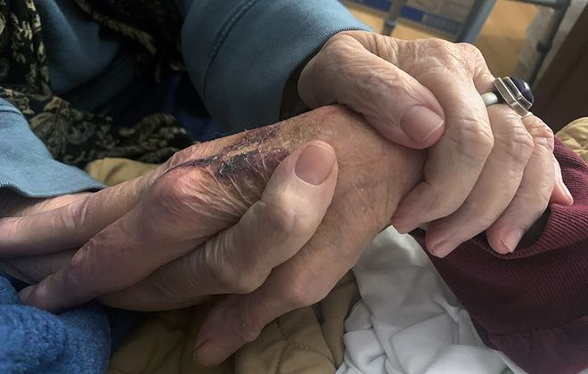 Charlee Clark holds the hands of her husband, Joseph Clark, at the Golden Gate nursing home in Cheektowaga shortly before he died on Sunday, March 29, 2020. (Photo courtesy of Jennifer Page)