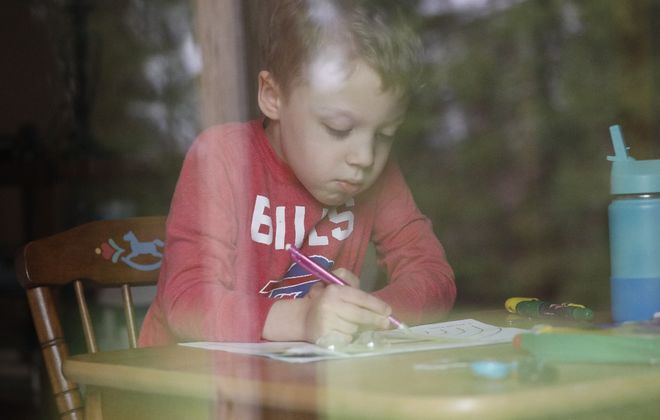 Jack Rosiek, 5, photographed through a window, labors on a masterpiece at the home of grandmother Mary Beth Rosiek in North Boston. His family is staying with his grandmother while their house in Eden is remodeled. (Derek Gee/Buffalo News)