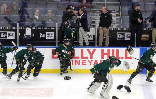Williamsville North coach Bob Rosen embraces one of his assistants on the bench after securing his 500th career win and the program's ninth federation hockey playoff championship. (John Hickey/Buffalo News)