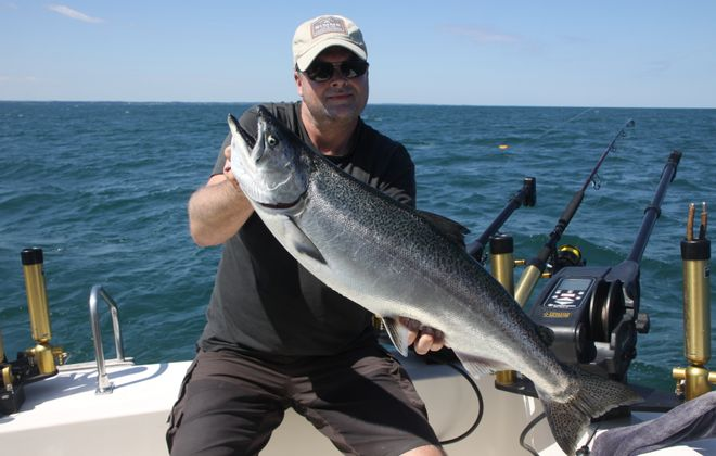 Thomas Kindel of Denmark shows off his first-ever Chinook salmon while fishing Lake Ontario out of Wilson with Capt. Mike Johannes of On The Rocks Charters. A new stocking strategy for the lake has been announced starting in 2020. (Bill Hilts, Jr./Buffalo News)