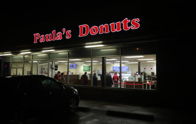 Customers gather for what could be the last time for a while this morning at Paula's Donuts on Sheridan Drive, in Town of Tonawanda. (John Hickey/Buffalo News)
