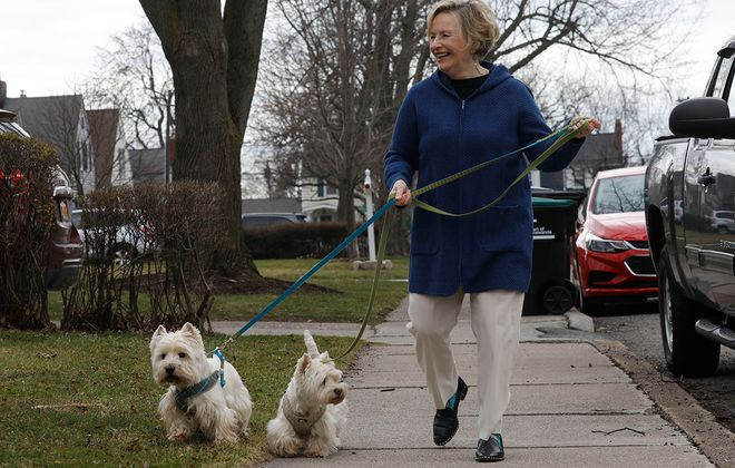 Licensed marriage and family therapist Kathy Calabrese, founder of Brain-Body-Health Technology Institute, walks with her Westies Finnegan and Tansey on Wednesday. It's part of her strategy to to exercise and address social isolation during the novel coronavirus pandemic. (Derek Gee/Buffalo News)