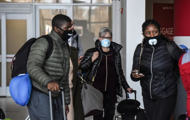 People wear masks at JFK Airport in New York on Feb. 27, 2020. (New York Times)