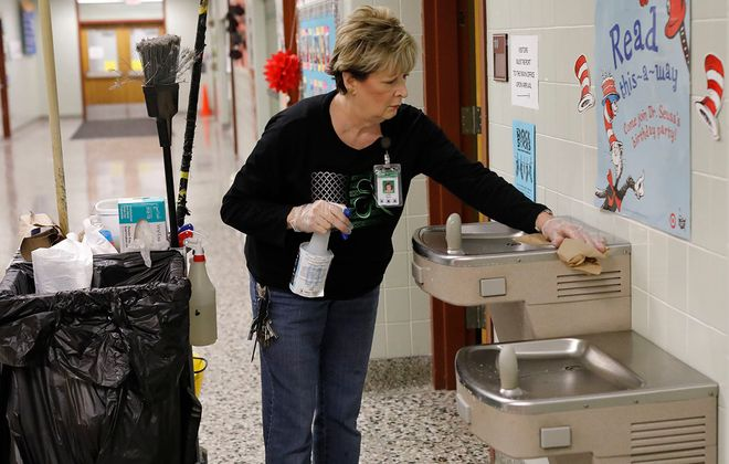 Custodian Linda Marth cleans the water fountains with disinfectant after school at Southside Elementary School, where many of the steps needed to prevent the spread of the new coronavirus are already part of the daily cleaning regimen. (Derek Gee/Buffalo News)