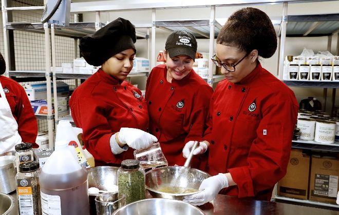 Students Siatta Webb, left, and Yaneishka Lebron, right, make a vinaigrette sauce under the watchful eye of teacher/chef Kristen Rodriguez during Thursday's grand opening of the Buffalo School of Culinary Arts & Hospitality Management on West Huron Street. (Robert Kirkham/Buffalo News)