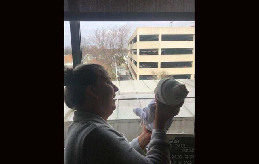 Kelsey Milley holds up newborn Nash Paul Milley so her dad can see his first grandson from the parking ramp at Mercy Hospital. (Family photo)