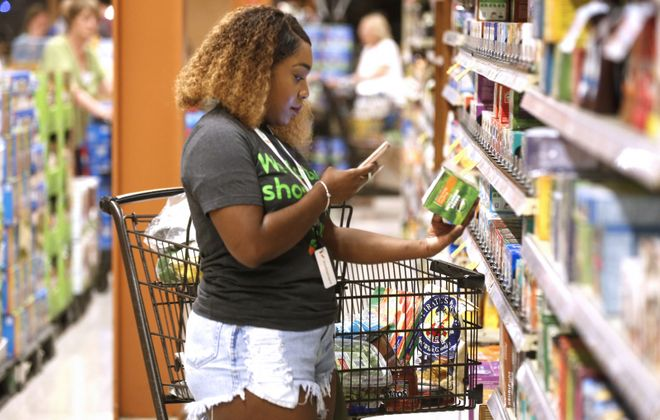 Professional shopper Brianna Johnson of Buffalo uses her smartphone and the app to shop and scan for a customer's order at the Wegmans location on Alberta Drive in Amherst in August 2017, when Instacart first came to the area. (Robert Kirkham/News file photo)