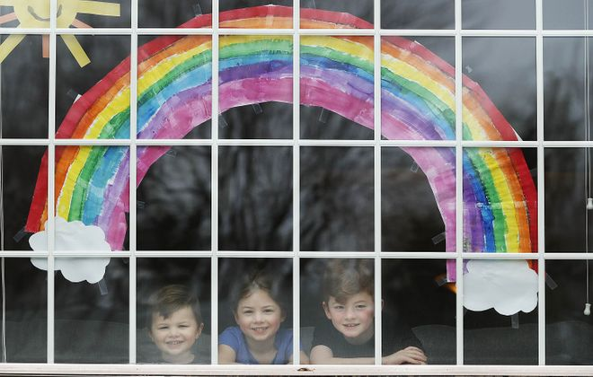 From left: Nolan, 3; Adeline, 5; and Declan, 7. The Mahoney children below a large rainbow hanging in the bay window at their Snyder home. (Sharon Cantillon/Buffalo News)