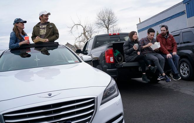Machelle and Todd Pohlman eat from the sunroof of their car. Alison Zuccala and her sons Ryan and Josh eat on the tailgate of their truck. It's all part of the Takeout Brigade's mission: gather en masse to order and eat takeout several times each week. (Derek Gee/Buffalo News)