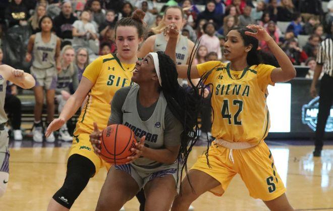 Niagara Purple Eagles forward Emerald Ekpiteta battles Siena Saints guard Sabrina Piper for the ball in the second half at the Gallagher Center Thursday (James P. McCoy/Buffalo News)