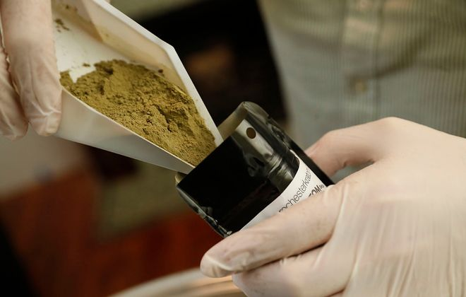 Matt McNeil of the Kratom Shop on Elmwood Avenue measures and packages some green kratom in October 2019. (Sharon Cantillon/News file photo)