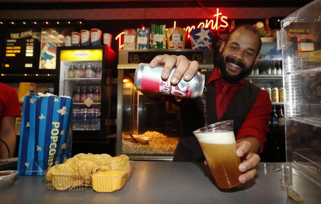 The Amherst Theatre started serving a limited selection of beer and wine along with new finger foods in November. Manager Greg Dickinson pours a Beltlien IPA beer for a customer who also ordered nachos and popcorn. (Sharon Cantillon/Buffalo News)