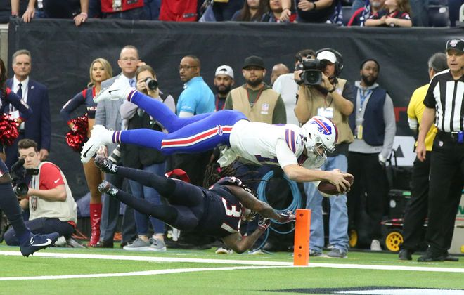 Bills quarterback Josh Allen dives into the end zone over Texans strong safety Jahleel Addae at NRG Stadium in Houston on Jan. 4, 2020. (James P. McCoy/Buffalo News)