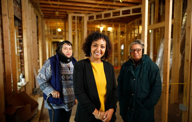PUSH Buffalo Executive Director Rahwa Ghirmatzion, center, with PUSH members and community advocates Luz Velez, left, and Providencia Carrion, right, at the Wash Project building at 417 Massachusetts Ave. where PUSH is rehabbing the century-old building into a 3-story with 9 apartments with the laundromat and Wash Project returning to space on the first floor, Friday, Jan. 3, 2020. (Derek Gee/Buffalo News)