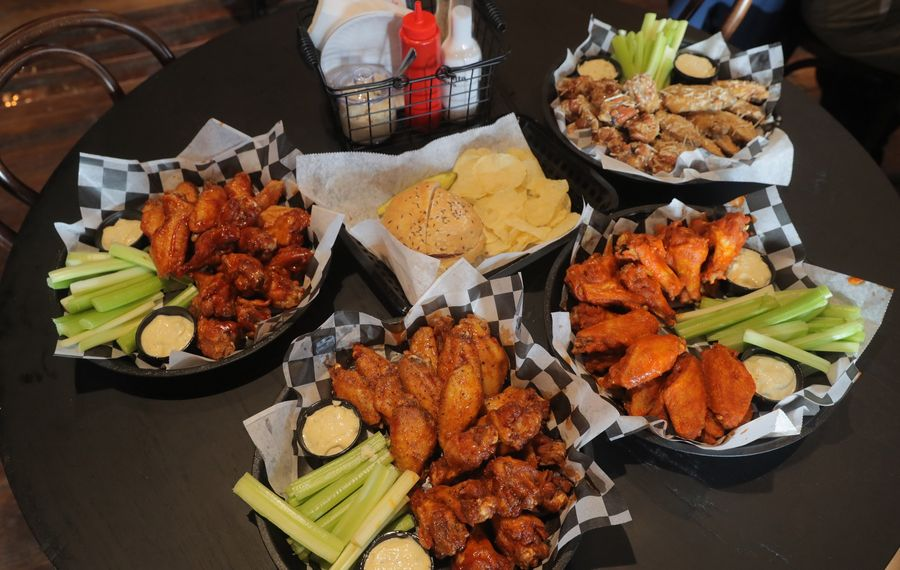 Served at the new Bar-Bill North are, clockwise from top left, Hot Spicy barbecue wings, beef on weck, Sicilian wings, hot wings and Cajun Honey Butter wings. (John Hickey/Buffalo News)