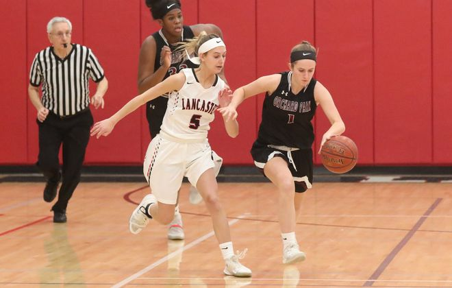 Orchard Park's Lily Flannery battles Lancaster's Alissa Backert for the ball in the first half at Lancaster High School in Lancaster, N.Y., on Monday, Jan. 13, 2020. Orchard Park won, 49-41. (James P. McCoy/Buffalo News)