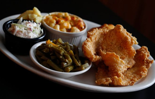 At PhatCatz,  the catfish dinner is served with mixed greens or green beans, cabbage, macaroni and cheese, potato salad, chef's choice cold salad and cornbread. (Sharon Cantillon/Buffalo News)