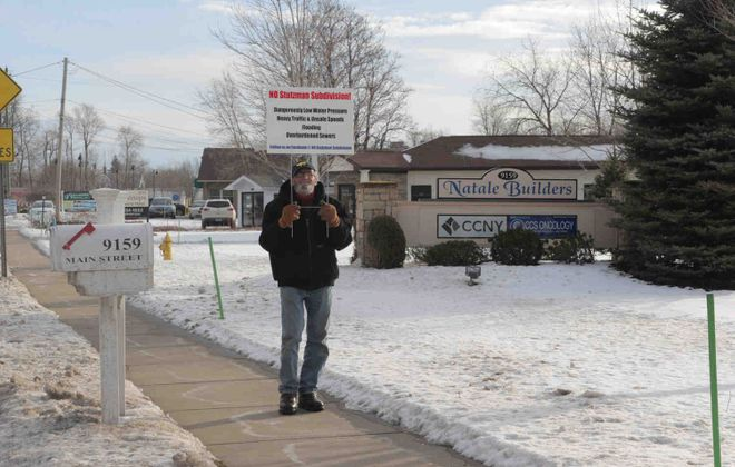 Lancaster resident James Ostroff protests a  subdivision proposed by  Natale Builders at their offices on Main Street in Clarence. (John Hickey/Buffalo News)