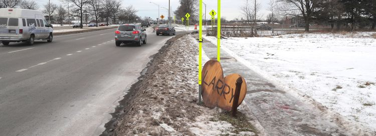 A wooden sign memorializes Larry Bierl, a homeless man known throughout Williamsville who froze to death at a bus shelter on Main Street in 2019. (John Hickey/Buffalo News)