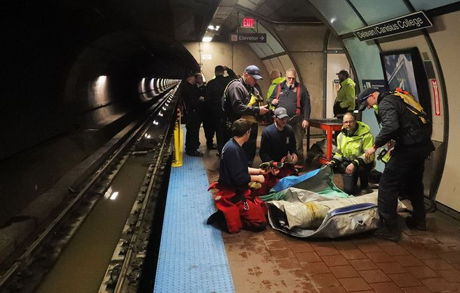 Buffalo firefighters from the Swift Water Rescue Unit and Rescue One deflate a raft on the platform at Delavan Station after investigating a water main break at Jefferson and Main Street flooded the station and created a river in the NFTA tunnel, leaving up to 8 feet of water on Thursday, Jan. 23, 2020. (John Hickey/Buffalo News)