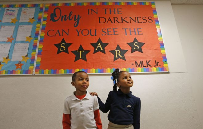 Students Jarod Jordan, 6, left, and Lauryiana Moore, 7, in a hallway with messages from the Rev. Martin Luther King Jr. at Charter School of Inquiry. (Robert Kirkham/Buffalo News)