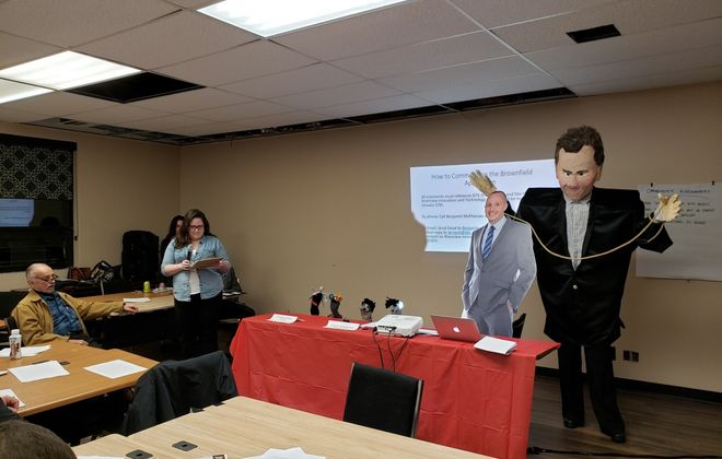 Members of the Clean Air Coalition present a cardboard cutout of state DEC Commissioner Basil Seggos tethered to a member wearing a papier mache likeness of Gov. Cuomo at public hearing Wednesday. (Harold McNeil/Buffalo News)
