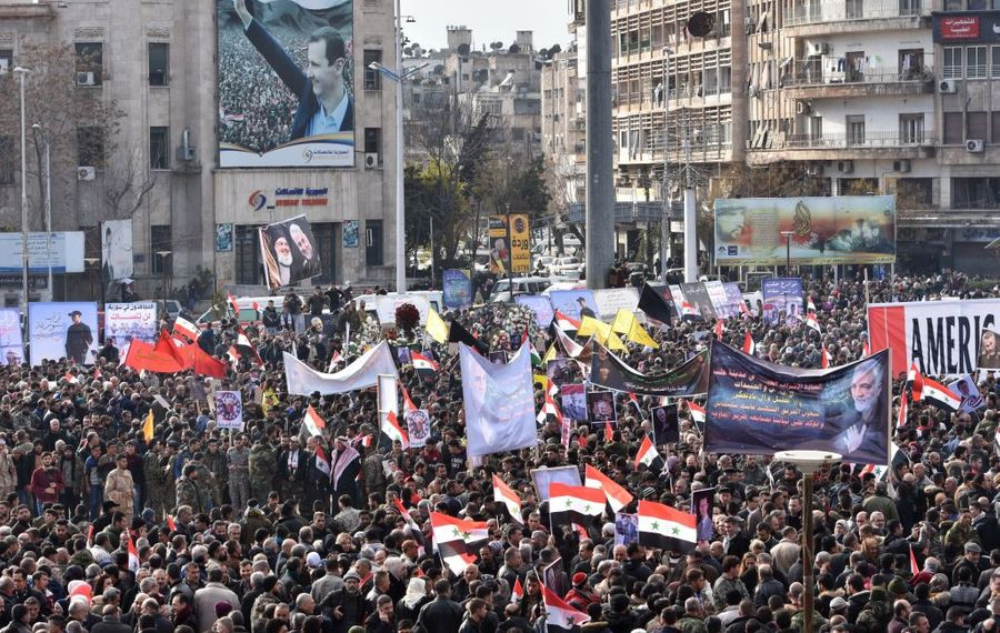 Syrian demonstrators and members of the military gather, under the portrait of Syrian President Bashar al-Assad, in the central Saadallah al-Jabiri square in the northern Syrian city of Aleppo on Jan. 7, 2020, to mourn and condemn the death of Iranian military commander Qasem Soleimani, and nine others in a U.S. air strike in Baghdad. (Photo by AFP via Getty Images)