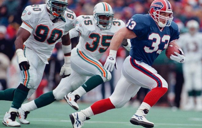 Bills' Tim Tindale runs away from Marco Coleman, left, and Michael Stewart of the Dolphins in AFC wild-card game in 1995. (Getty Images file photo)