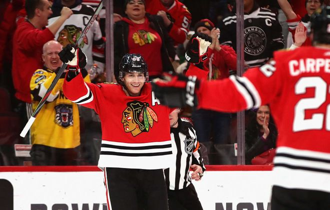 Patrick Kane celebrates his 1000th career point, an assist on a goal by Brandon Saad in the third period of Sunday's win over Winnipeg in United Center (Getty Images).