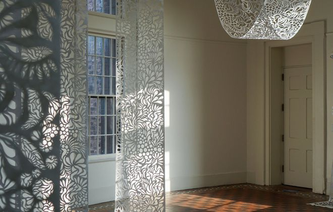 """""""Ethereality"""" is a site-specific installation from multimedia artist Kari Achatz, who created intricately cut Tyvek scrolls to hang and drape between light fixtures at Hotel Henry."""