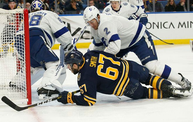 Buffalo Sabres forward Dalton Smith (67) gets taken down by Tampa Bay Lightning defenseman Luke Schenn (2) as he goes to the net during the first period at KeyBank Center, Tuesday, Dec. 31, 2019. (Derek Gee/Buffalo News)