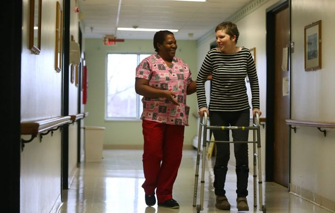 Certified nurses aide  Falanda Stevenson works with resident Erin Deming at Safire Rehabilitation of the Southtowns nursing home in Buffalo on Dec. 23, 2014.  (Mark Mulville/News file photo)
