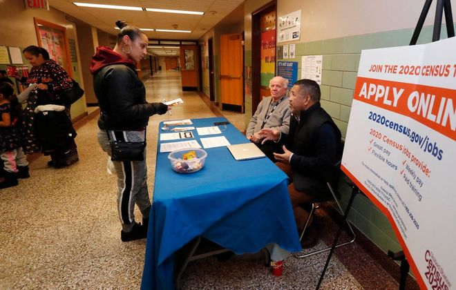 Larry Smith, center, and Phil Pandy, right, from the U.S. Census Bureau talk with Cristaliz Orozco, left, at Frank Sedita Academy on Dec. 14, 2019. (Sharon Cantillon/Buffalo News)