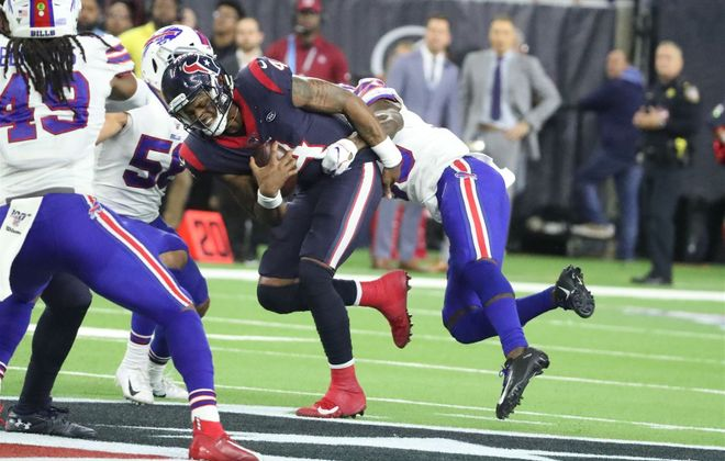 Buffalo Bills defensive back Siran Neal (33) thought he had sacked Houston Texans quarterback Deshaun Watson (4), but he was able to get away and throw to Texans running back Taiwan Jones (34) for a first down in overtime. (James P. McCoy/Buffalo News)